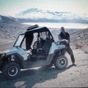 My best friend, Brian, by the RZR on the mountain behind our house. You can see our sub division in the background on the left.  I think my house is s